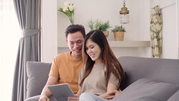 Azjatycka para używa pastylkę dla online zakupy w internecie w żywym pokoju w domu, słodka para cieszy się