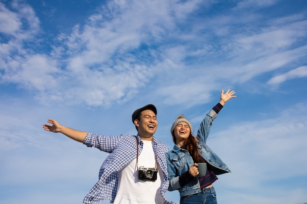 Azjatycka para w błękitnej koszula z filiżanką i rocznik kamery pinkinem na górze blisko plażowego dennego widoku szczęśliwego i uśmiechu twarzy