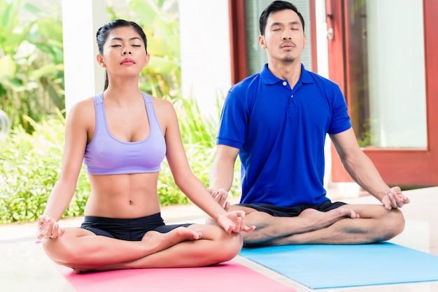 Azjatycka para w lotosu siedzenia joga pozie ćwiczy