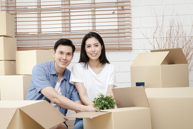 Azjatycka para wprowadza się do nowego domu pomóż rozpakować brązowe papierowe pudełko, aby udekorować dom. koncepcja rozpoczęcia nowego życia, zbudowania rodziny. skopiuj miejsce
