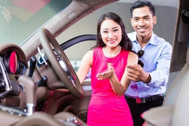 Azjatycka para wybiera luksusowy samochód w salonie samochodowym patrząc na wnętrze