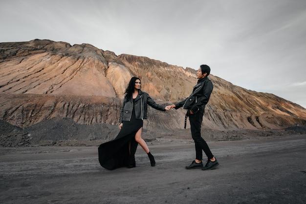 Azjatycka para zakochana w czarnej skóry ubraniach chodzi w naturze. miłość, szczęście