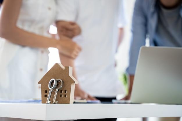 Azjatycka para zdecyduj się na zakup nowego domu od laptopa z agentem nieruchomości, przedmiotem jest model domu z kluczem