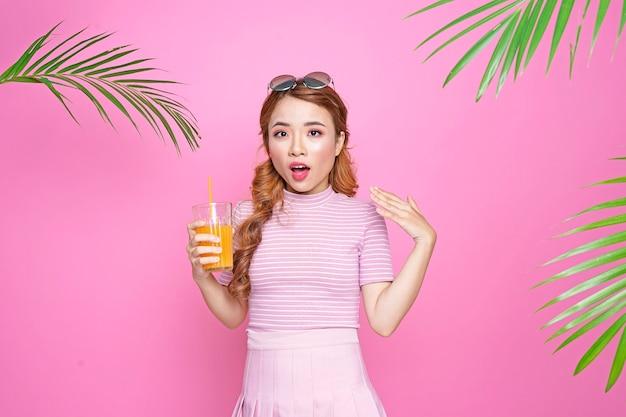 Azjatycka piękna atrakcyjna ładna młoda dziewczyna w koncepcji lato z soku pomarańczowego i liści palmowych