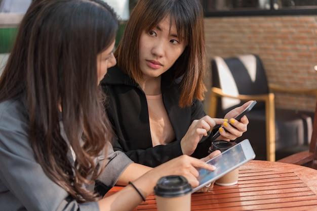 Azjatycka piękna biznesowa kobieta pracuje z pastylką i smartphone w kawowej kawiarni sklepie