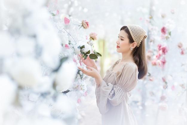 Azjatycka piękna dziewczyna ubrana w kremową sukienkę uśmiecha się i stoi w białym różanym ogrodzie kwiatowym jako naturalna