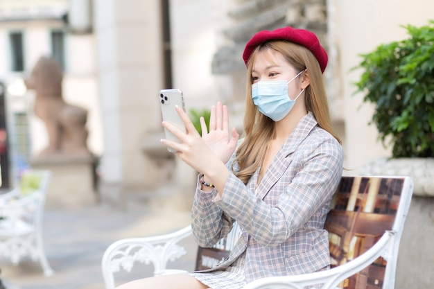 Azjatycka piękna famale w garniturze i czerwonej czapce trzyma w dłoniach smartfona do wideorozmowy, gdy siedzi na ławce w parku, mając na sobie medyczną maskę na twarz w opiece zdrowotnej, zanieczyszczenia pm2,5, nowe normalne i