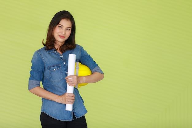 Azjatycka piękna inżynierka niosąca białą rolkę papieru i trzymająca żółty bezpieczny kask, stojąca przed kolorowym zielonym tłem