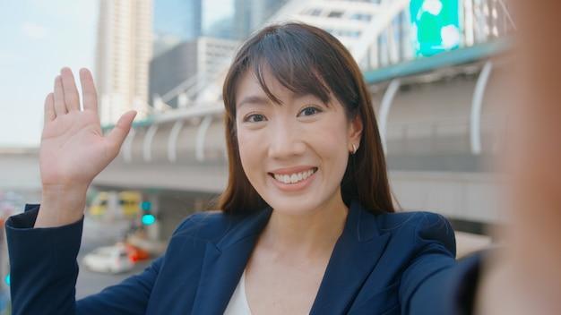 Azjatycka piękna kobieta biznesu nawiązuje połączenie wideo z kolegami lub rodziną w nowoczesnym mieście, współpracy biznesowej i koncepcji technologii biznesowej.