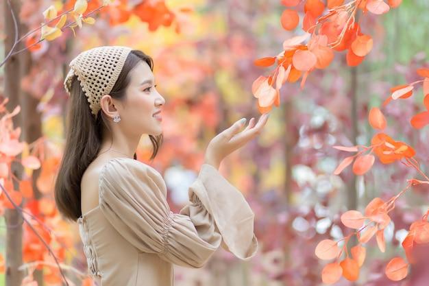 Azjatycka piękna kobieta, która nosi jasnobrązową sukienkę stoi i uśmiecha się szczęśliwie z pomarańczowym lasem