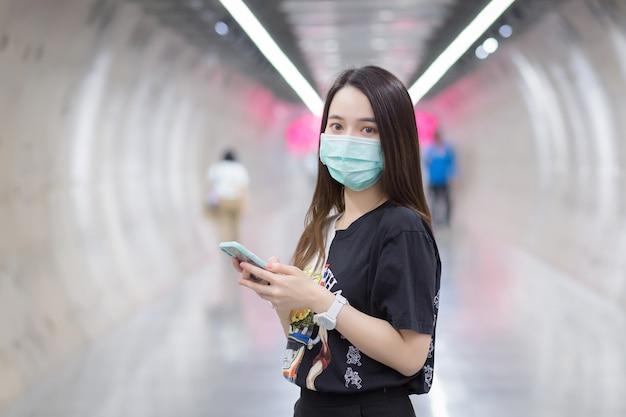 Azjatycka piękna kobieta nosi czarną koszulę i medyczną maskę na twarz, gdy wchodzi do tunelu metra