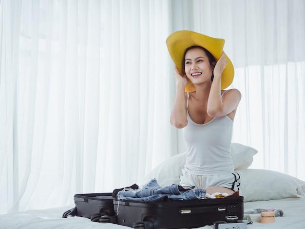 Azjatycka piękna kobieta przygotowywa torby iść na wakacje