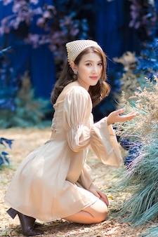 Azjatycka piękna kobieta siedzi na ziemi i podziwia kwiat w niebieskim ogrodzie i lesie jako tło.