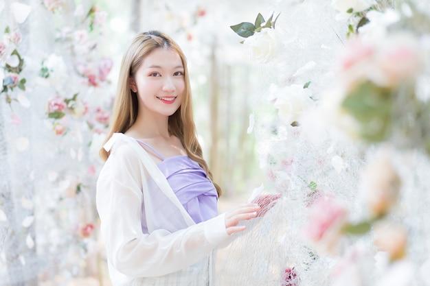 Azjatycka piękna kobieta ubrana w biało-fioletową koszulę uśmiecha się i stoi w białym różanym ogrodzie kwiatowym