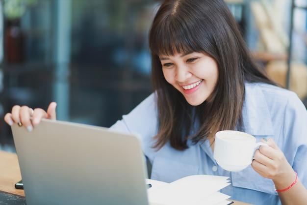 Azjatycka piękna kobieta w błękitnej koszula używać laptop i pijący kawę