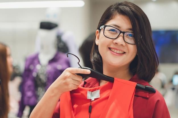 Azjatycka piękna kobieta wybiera kupować nowego set nadaje się dla sezonu, sezonu