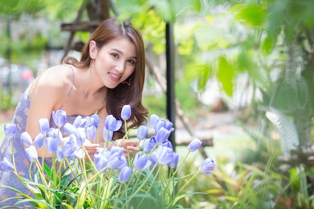 Azjatycka piękna kobieta z długimi włosami stoi pośród fioletowych kwiatów tulipanów i zielonego ogrodu