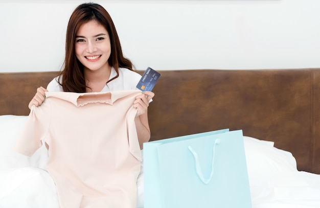Azjatycka piękna kobieta zaskoczona papierowymi torbami z towarami z radosną, uśmiechniętą twarzą, będąc nowym, normalnym biznesem online w zakupach z domu