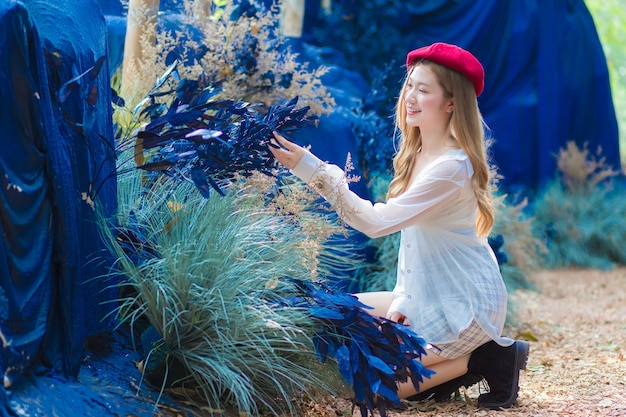 Azjatycka piękna młoda kobieta siedzi i wygląda na niebieski kwiat w naturalnym ogrodzie kawiarni.