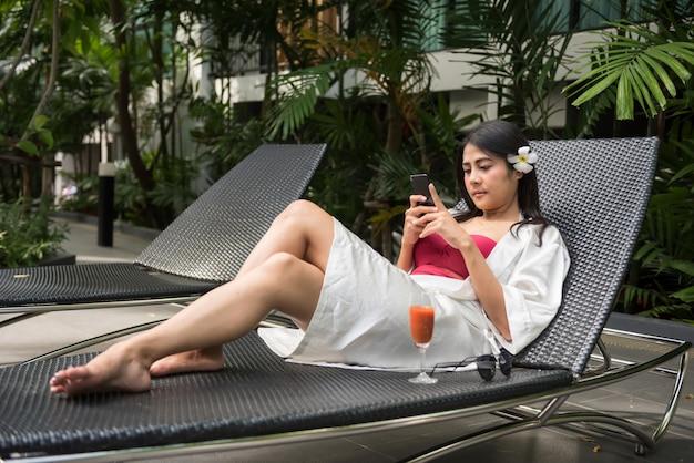 Azjatycka piękna młoda kobieta w czerwonym jednoczęściowym stroju kąpielowym na łóżku grać w mediach społecznościowych, rozmawiać przez telefon na basenie. kobiece dziewczyny zrelaksować się w letnie wakacje w luksusowym hotelu.