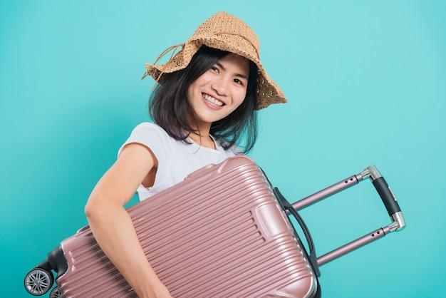 Azjatycka piękna młoda kobieta w koncepcji podróży wakacje, jej przytulanie torbę z walizką