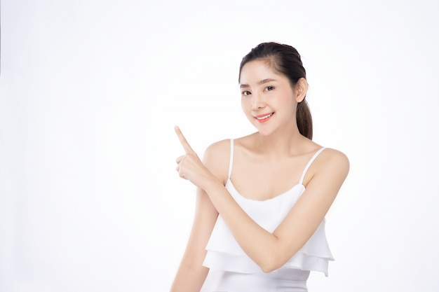 Azjatycka piękna młoda kobieta wskazuje jeden rękę z palcem na górnej stronie z uśmiech twarzą