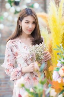Azjatycka piękna pani patrząc na kwiaty trzyma w ręku z naturalnego tła.