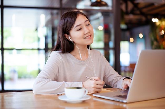 Azjatycka piękna pracująca kobieta robi swoją pracę i pije w kawiarni lub kawiarni.