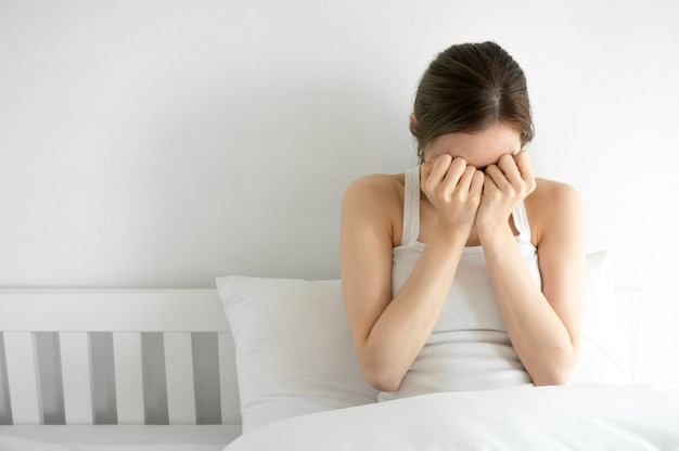 Azjatycka piękno kobieta płacze na białej sypialni w ranku