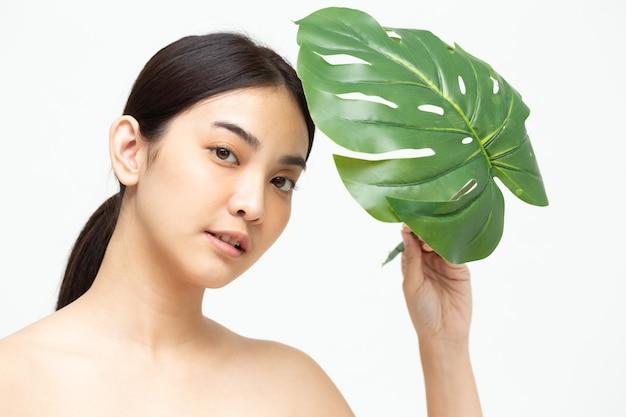 Azjatycka piękność kobiety z naturalnym zielonym liściem na białym tle
