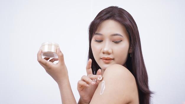 Azjatycka piękność ocierająca się o ramię na białym tle