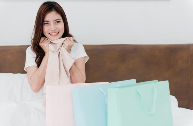 Azjatycka piękność zaskoczona papierowymi torbami z towarami z radosną, uśmiechniętą twarzą, będąc nowym, normalnym biznesem online w zakupach z domu