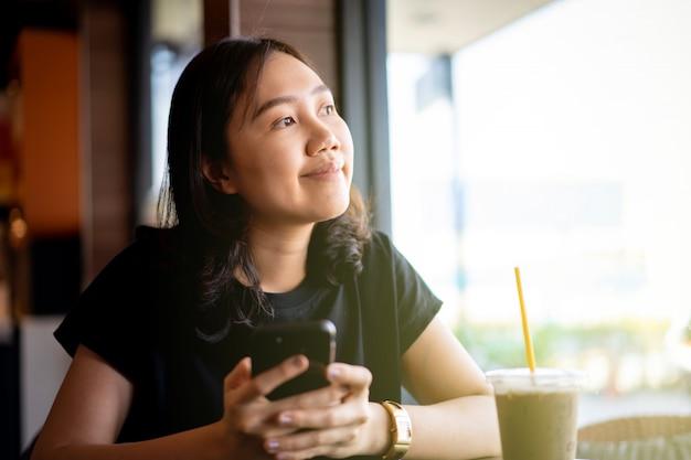 Azjatycka pochodzenie etniczne młoda kobieta relaksuje mrożoną kawę i pije przy sklep z kawą. kobieta używa smartphone wysyłać wiadomość podczas gdy pijący kawę w kawiarni i restauraci zamkniętej up z copyspace.