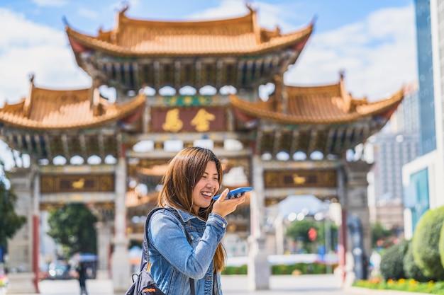 Azjatycka podróżniczka korzystająca z inteligentnego telefonu komórkowego do nagrywania poleceń głosowych podczas podróży przez plac jinbi, kunming, chiny, podróże i turystykę, słynne pojęcie miejsca i atrakcji