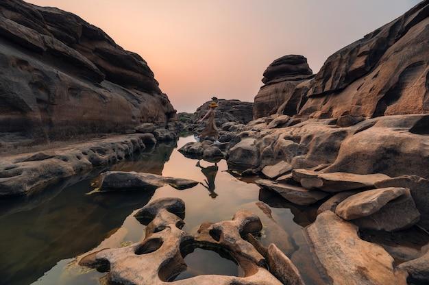 Azjatycka podróżniczka skacząca po skalistych bystrzach w geologicznym wąwozie w hat chom dao