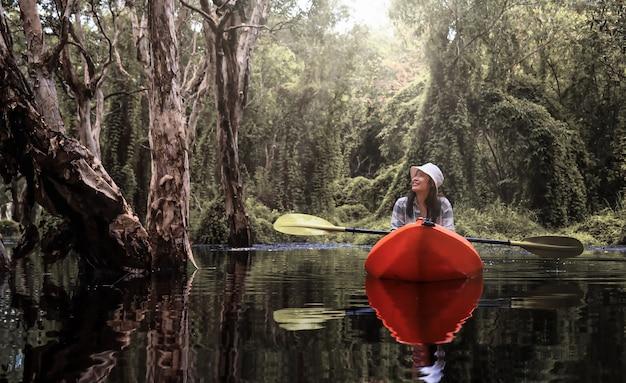 Azjatycka podróżniczka spływa kajakiem po lesie namorzynowym w ogrodzie botanicznym tajlandii