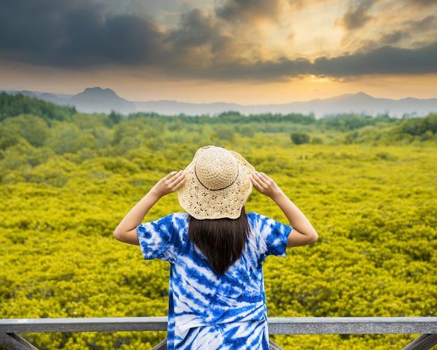 Azjatycka podróżniczka trzymająca kapelusz i stojąca na drewnianym moście do podróży