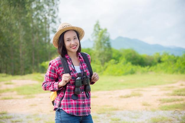 Azjatycka podróżnik kobieta chodzi w lesie z plecakiem i lornetkami.