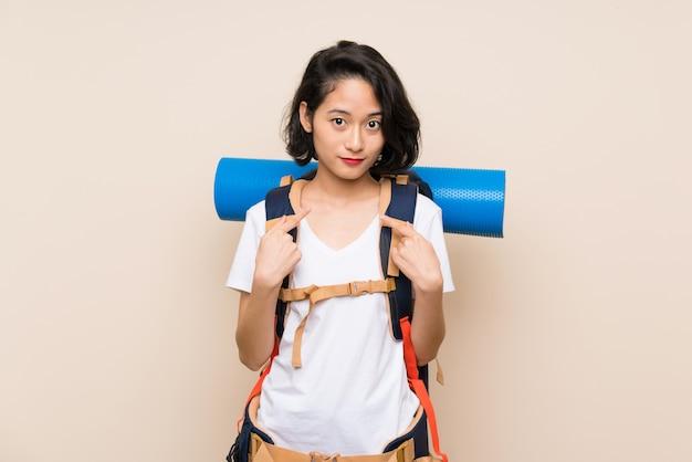 Azjatycka podróżnik kobieta nad odosobnioną ścianą z niespodzianka wyrazem twarzy