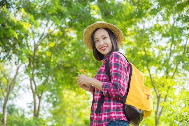 Azjatycka podróżnik kobieta z plecaka odprowadzeniem w lesie, trzyma dzikiego kwiatu i ono uśmiecha się