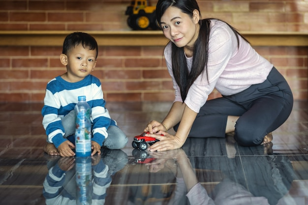 Azjatycka pojedyncza mama z synem bawić się z samochód zabawką wpólnie gdy żyjący w nowożytnym domu