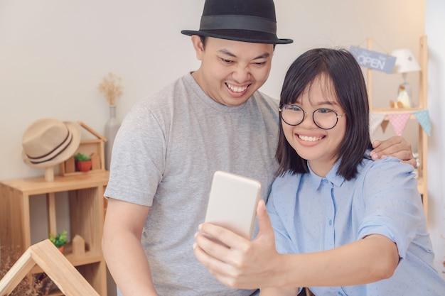 Azjatycka potomstwo para bierze selfie z szczęście akcją w nowożytnym sklep z kawą lub workpl