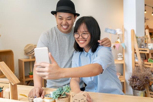 Azjatycka potomstwo para bierze selfie z szczęście akcją w nowożytnym sklep z kawą