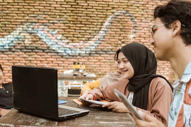 Azjatycka potomstwo para używa jej laptopu i pastylki komputer osobistego