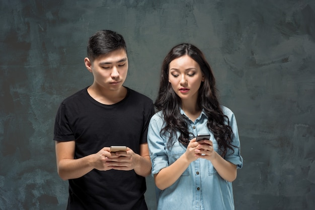 Azjatycka potomstwo para używa telefon komórkowego, zbliżenie portret.