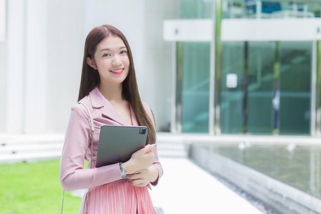 Azjatycka profesjonalna biznesowa kobieta z długimi włosami uśmiecha się na zewnątrz w ogrodzie przed biurem, trzymając tablet w dłoni, aby wyjść na spotkanie z klientami w biurze, pracować od każdej chwili