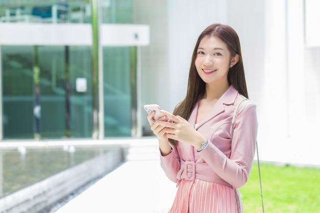 Azjatycka profesjonalna biznesowa kobieta z długimi włosami uśmiecha się przed biurem