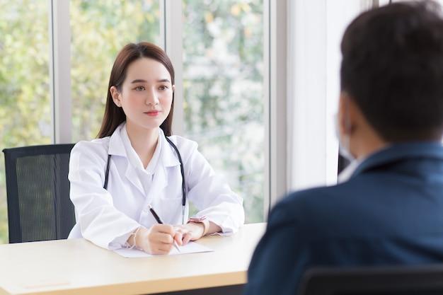 Azjatycka profesjonalna lekarka, która nosi płaszcz medyczny, rozmawia z pacjentem, aby się skonsultować