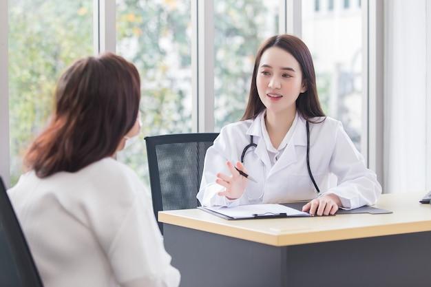 Azjatycka profesjonalna lekarka, która nosi płaszcz medyczny, rozmawia z pacjentką