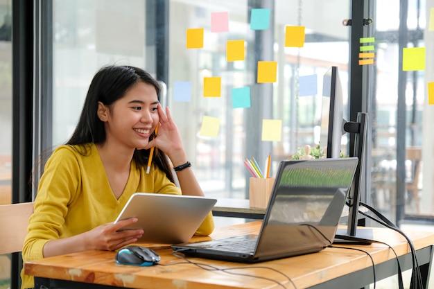 Azjatycka programistka, ubrana w żółtą koszulkę, patrząca na ekran laptopa, trzymająca tablet i ołówek. wydawała się szczęśliwa.